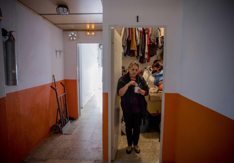 Rosario Planas desayuna apoyada en la puerta del trastero en el que vive, en el barrio de Torrefiel